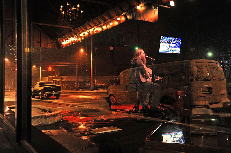 "As snow falls outside, ""One man band"" Albert Simpson performs during his gig at The Brick Deli & Tavern Wednesday, February 9, 2011. Simpson drove all the way from Gadsden and, because of the snow storm, was planning to sleep in his van (reflected in the window glass)."