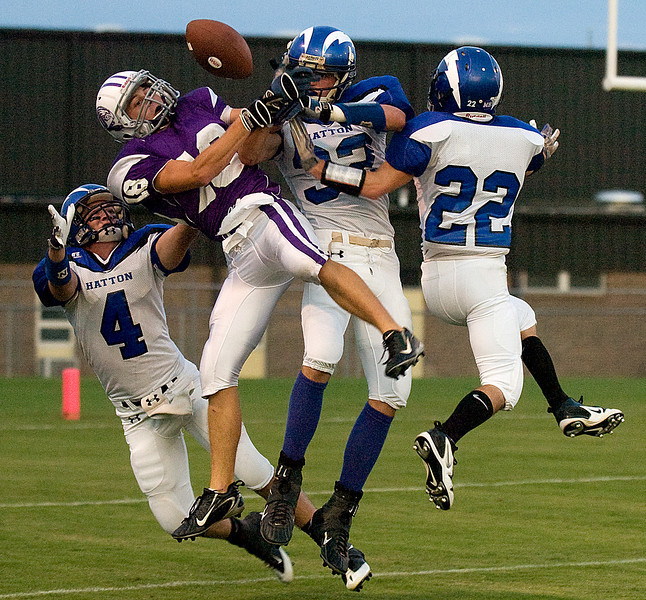 Danville's Tyler Beck, second from left, struggles over a pass with Hatton's  Jordan Montgomery (4), Curtis Ard (32) and David Mims (22) during the first quarter of the game at Danville High School Friday, August 27, 2009.