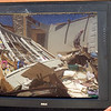 What used to be Dorothy Humphries' living room before the April 27 tornadoes is reflected in a TV screen as her brother-in-law, 84-year-old Nathaniel Conley, wanders through the rubble in Eastern Morgan County, Ala. Friday, April 29, 2011.