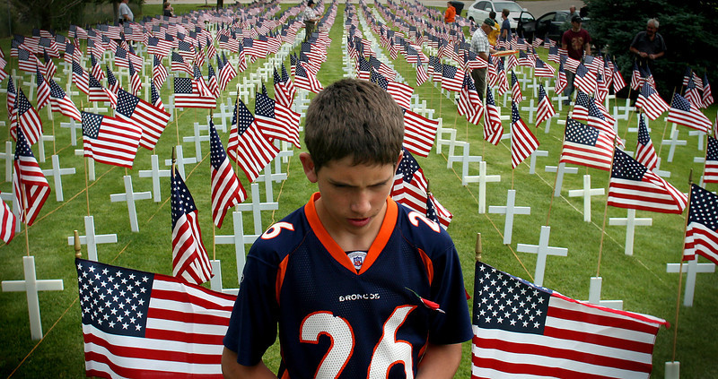 Trevis Rowley, 13, takes one more look to make sure that everything is lined up on one of the three plots where war veterans and volunteers put up 1,170 crosses and flags in preparation of Memorial Day in Orem Cemetery, Thursday May 24, 2007.<br /> Eighty-eight new flags have been added this time, one for each war veteran passed away over the last year.