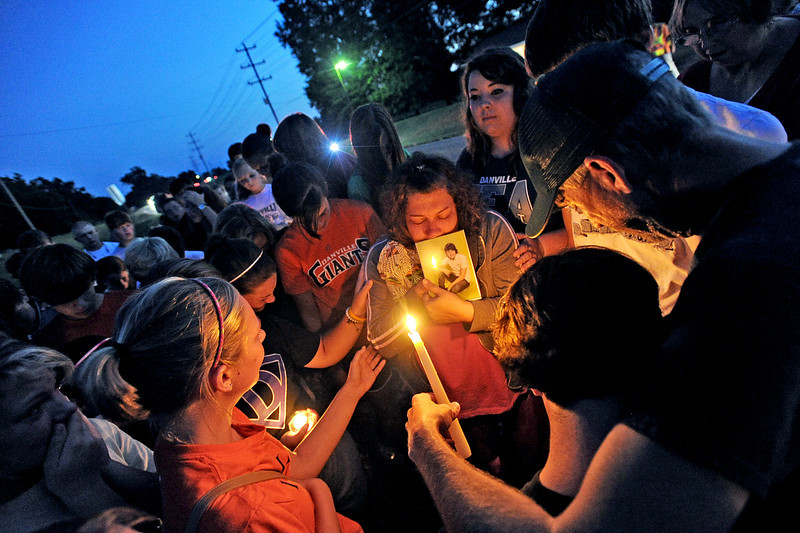 Classmates and friends of Jacob Birdwell gather around his mother, Fran, center (holding Jacob's picture) and father, Greg, right, to pray during a candlelight vigil held on the spot where he was killed in an accident on Danville Rd. earlier on Wednesday, August 17, 2011.