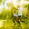 "Sunlight is filtered through a cloud of yellow powder as two runners compete in the ""Color Your World"" 5K run at Oakville Indian Mounds Park Saturday, June 8, 2013."