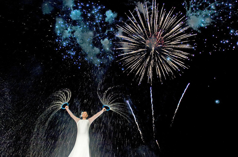 Tiffani Adamson performs a water dance as fireworks fill the sky during the grand finale of the 5th annual Luau at Point Mallard Friday, June 25, 2010.