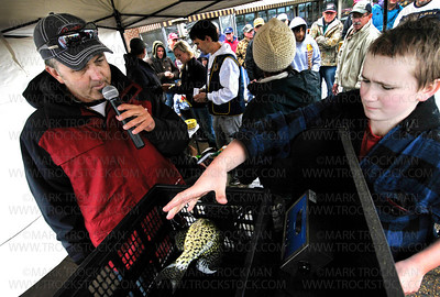 Emcee and official Lions Club Crappie Fishing Contest weigh-in Grand Poobah Mark Schutz, left, of Full Throttle Fishing in Brooklyn Park, keeps the crowd outside Maynard's restaurant informed while volunteer Sam Bissen, 12, drop a fish onto the scale Saturday, April 21, in Excelsior.