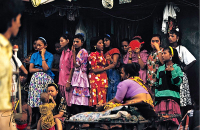 CAGE Nepali sex workers and a 'madam' waiting for clients in front of the legendary 'cages' on Falkland Road, in Mumbai's working-class brothel district. It is the destination of many trafficked children and women from Nepal. Contrary to the myth of Nepali girls being coveted for their grace and beauty, they are imported to India because they are sold cheaply on the market.  Falkland Road, Mumbai, India.