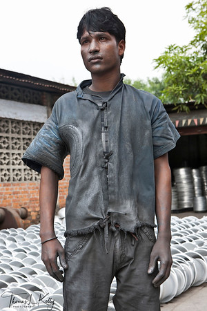 """APPRENTICE  An apprentice since he was thirteen-years-old, Yadav followed his master to Nepalgunj and overtime, mastered the machines. He now oversees his unit and produces over 500 water basins a day. When asked what he dreams to be, he says, """"to be a teacher at the technical school.""""  Nepalgunj Industrial Estate, Nepal."""