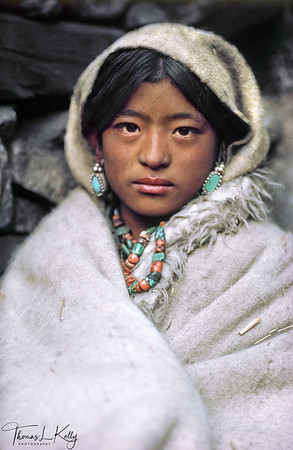 "NAMDOL  Namdol's father died at an early age, and her widowed mother traveled the trading routes of far Western Nepal to try to support her four children. Namdol grew up with her grandparents in a cave above the village of Yakpa in Humla. At age 10, with foreign sponsorship, Namdol enrolled in Mt. Kailas boarding school in Kathmandu. Unmarried at the age of  15, she  gave birth to her son Lobsang Tsumde, the offspring of an encounter on a return visit to the village, interrupting her short educational career.  ""If I knew more about contraception, or maybe if I had been uglier, my life would have been very different,"" she says.  Humla, Northwest Nepal."