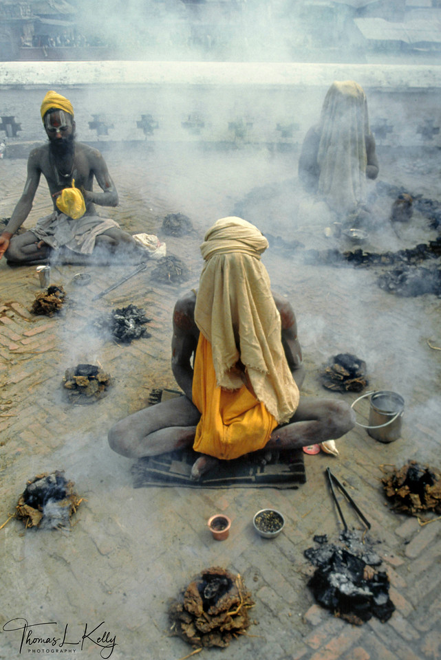 """A group of sadhus engage in an ancient practice called the panch-agni-tapasya, or five fire austerity, in this photograph. During this austerity, the ascetic surrounds himself with four cow dung fires, taking the sun as the fifth, repeatedly chants name of his chosen deity with the aid of a mala, hidden under a cloth. Over a cycle of eighteen years, the sadhu increases the number of fires to a full ring of """"innumerable"""" fires that is never completely closed, allowing the God to enter. In the final stage, a pot of burning cow dung is held on the sadhu's head. Usually practiced during the height of summer heat, the sadhu's ability to remain focused on his chosen mantra and deity is severely tested. The intention of this ritual is for the sadhu to symbolically sacrifice himself to the fire, ultimately becoming an offering to God.<br /> <br /> This austerity is connected to the small sacred fire (dhuni) that many sadhus keep as the focal point of all daily worship rituals and religious practices, and a potent symbol of the ascetic's self-sacrifice, rebirth from ashes, and the ash-covered Shiva."""