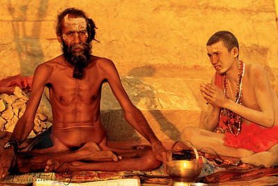 In this photograph, a disciple (chela) pays homage to his guru, who in turn gives his blessing. The relationship between guru and student begins as one of obedience and servitude. Once the disciple is deemed fit for the ascetic life, he will be given initial instructions and prepared for initiation. Though they often differ between sects, initiations all center round the idea of rebirth: the chela severs all ties with his earthly life, symbolically dying as a human and then is reborn into the divine life. His guru gives the initiate a new name reflective of his new holy family and status, imparts a powerful, personal mantra. The chela serves and worships his guru as god-incarnate, as in this photograph, whereas the guru takes full responsibility for his disciple's spiritual education and earthly life, including his bad karma.  Large festivals like the Kumbh Mela often provide a chance for students to meet their teachers in order to check in and receive further instructions. A young disciple will travel and study with his teacher for years.