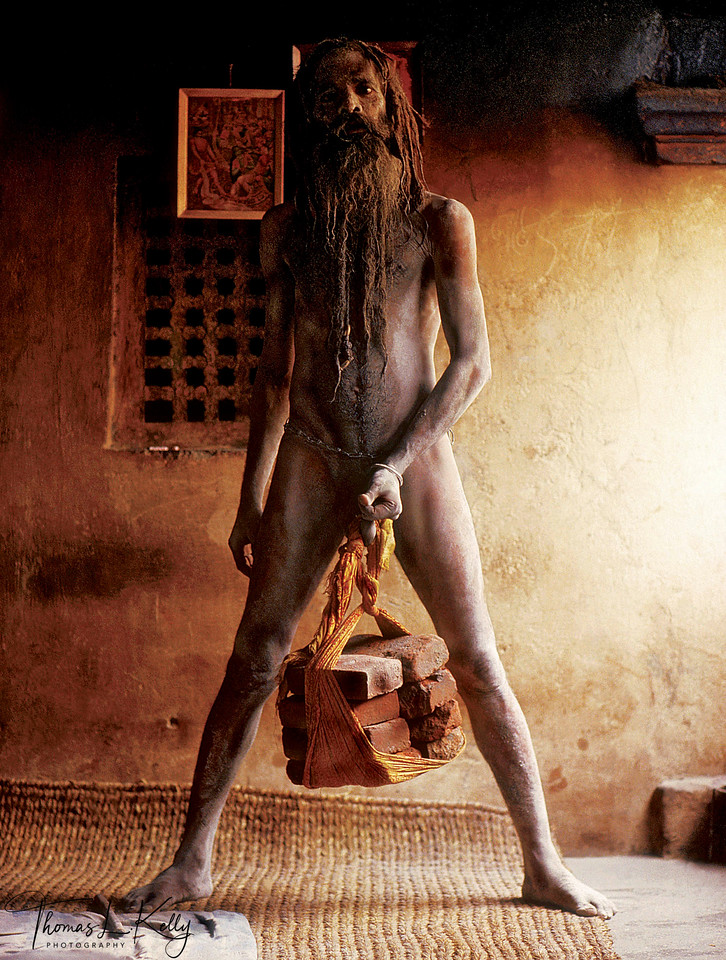 """Sadhus wishing to expedite the process of enlightenment may choose to perform severe austerities and mortifications. Even at age sixty-six, Pagalinanda Aghori Baba can demonstrate the Naga practice of """"penis yoga,"""" which is based on the complete transcendence of sexual impulses. After a preliminary, nine-year period of self-imposed celibacy, the yogi is truly initiated during a ritual in which certain nerves of the penis are broken, enabling him to """"lift"""" rocks weighing over one hundred pounds. However, the initiation ceremony for this practice makes it highly unlikely he will ever have another erection.<br /> <br /> It is essential for the ascetic to sublimate and control all desire, especially sexual, in order to maintain his spiritual power. An alternative method frequently employed to aid in the control of passion is the use of chastity belts, either wooden or metal. Such extreme practices are not only performed to control desire, but also to eliminate other spiritual obstacles: the pleasure of eating is destroyed by only drinking milk and attachment to the body is severed by standing for twelve years."""