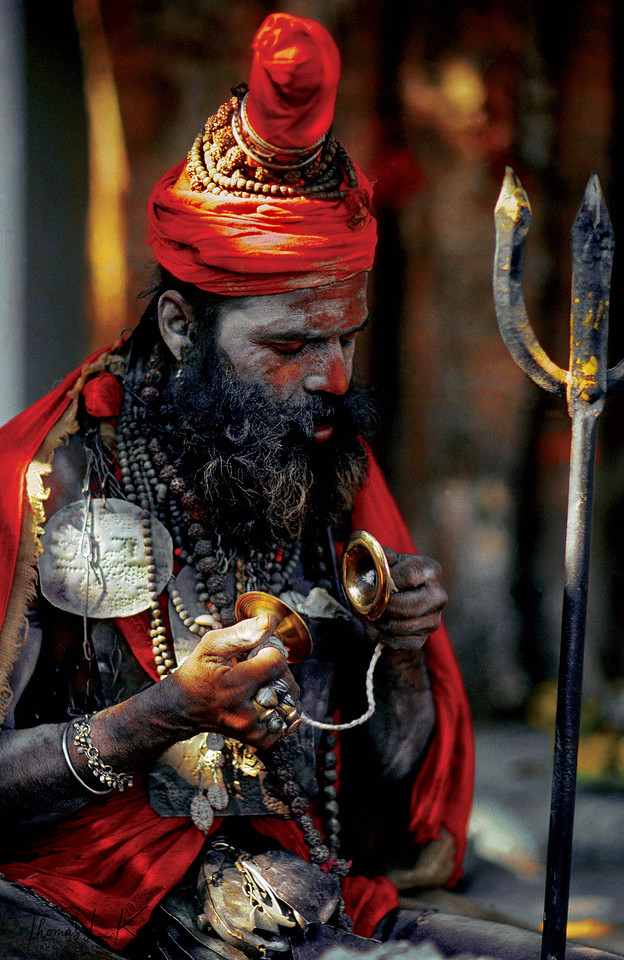 Shiva is a god of countless manifestations and a variety of forms, each famed for certain attributes, deeds and powers, and the Shaiva sadhus seek to emulate the image of the deity outwardly, while working toward internalizing the god's being and knowledge through ritual and spiritual practice. On the surface, this sadhu adopts the characteristics of Shiva: he sanctifies the body with sacred ash tilaka, wears his hair in matted locks to evoke yogic power, and carries the god's iconic trident (trishul), the weapon that connects heaven and earth. On a deeper level, however, the sadhu performs all daily activities, both sacred and mundane, as rituals dedicated to the Divine, thus transforming his whole existence into holiness. The sadhu seeks to be like Shiva and finally be in complete union with him.<br /> <br /> Because the sadhus imitate the gods in appearance and behavior, they are perceived and worshiped as living idols with the ability to accumulate and channel spiritual energy to the laity.