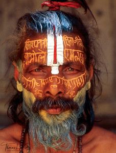 While some sadhus value a more energetic and impressionistic approach to tilaka, others value precision and complexity in their body art, such as the ascetic pictured here, who has written sacred text, likely mantra or hymn, across his face. This unique tilaka might be an act of devotion to his tutelary deity, offering a prayer to Vishnu as part of his daily activities. However, painting the efficacious syllables of an esoteric mantra on the body might suggest more magical motivations.  Mantras have myriad meanings and uses, both public and secret, including magical incantations for healing, invocations requesting the presence of a god, primordial sounds of Creation and the Absolute, and repetative prayer aimed at focusing the mind on a deity. During a sadhu's initiation, his guru imparts to him a powerful, personal mantra, which is never spoken aloud. This mantra established the psychic bond between teacher and student, through which guidance may be asked for and issued.