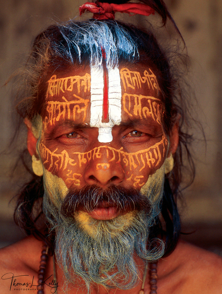 While some sadhus value a more energetic and impressionistic approach to tilaka, others value precision and complexity in their body art, such as the ascetic pictured here, who has written sacred text, likely mantra or hymn, across his face. This unique tilaka might be an act of devotion to his tutelary deity, offering a prayer to Vishnu as part of his daily activities. However, painting the efficacious syllables of an esoteric mantra on the body might suggest more magical motivations.<br /> <br /> Mantras have myriad meanings and uses, both public and secret, including magical incantations for healing, invocations requesting the presence of a god, primordial sounds of Creation and the Absolute, and repetative prayer aimed at focusing the mind on a deity. During a sadhu's initiation, his guru imparts to him a powerful, personal mantra, which is never spoken aloud. This mantra established the psychic bond between teacher and student, through which guidance may be asked for and issued.