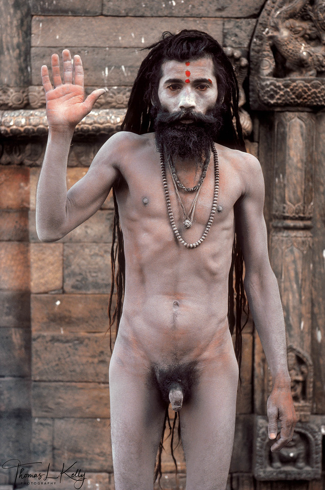 """This ash-covered sadhu, a member of the Naga sub-sect, holds up his right hand in the abhaya mudra, which expresses """"have no fear"""" and grants a blessing. Nudity is the ultimate expression of asceticism, for it represents an absolute renunciation of the material world and its attachments, as well as a complete transcendence of sexuality and the sensual body. Remaining nude or semi-nude in all weather conditions is considered a severe austerity and an emulation of Shiva, who himself is digambara or """"sky clad."""" Naked ascetics seem to have been ubiquitous before British rule, but nowadays only fully initiated Shaiva Nagas can go nude and typically only for special occasions. <br /> <br /> Both Shaivas and Vaishnavas cover themselves in sacred ashes, or vibhuti, like this Naga Baba. Vibhuti is usually taken from the sadhu's own sacred fire, that of a temple or, most potently, cremation fires. Considered the prasad, or """"food,"""" from the god of Fire, the vibhuti represents to the sadhu the conquering of death and the destruction of his karma in the fire of austerity."""