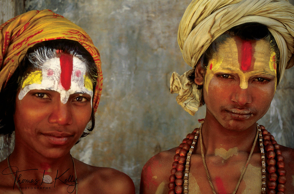 Mundane motives often mix with spiritual aspirations when a person decides to join the brotherhood of sadhus. Asceticism not only offers a life devoted entirely to religious study and the possibility of spiritual attainment, but also one that is free from the social bonds of family and the restrictions of caste. Boys in early adolescence, like the young sadhus in this photograph, can be adventurous in their abandonment or simply practical, having few other options if they are orphaned or impoverished. <br /> <br /> These two young Vaishnavas with colorful tilaka perhaps chose the life of a sadhu over that of a lower caste member, or a family tragedy may have forced them into this role. Regardless, they are better provided for and will have more opportunities than many of the poor and homeless in South Asia. Renouncing his birth family for one of the Hindu gods, a young sadhu adopts as his new family Vishnu, Brahma or Shiva as well as his guru and brother sadhus.