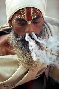 Although Hindu religious texts as well as sadhus themselves hold varying opinions about drug use as a spiritual practice, it is important to many sadhus, including the one pictured here. He is most likely smoking a mixture of tobacco and hashish, or charas, in a straight clay pipe called a chilam. Because the god Shiva is admired for his ability to transmute poisonous substances into harmless or beneficial elements, drug use is seen by many to be an important spiritual practice unto itself. Shiva is invoked before the first puff and the intoxicating properties are felt to be the blessings of Shiva, Lord of Charas, and a means of attaining divine wisdom and partaking in Shiva's ecstasy. As a final gesture of devotion, a sadhu may mark his forhead with chilam ash.  While smoking itself is considered an austerity demonstrating non-attachment to the body, it also is a communal ritual between sadhus and devotees.