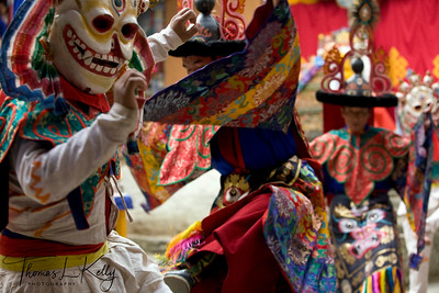 Thur-dhag, the dance of Liberation, is the central act of the sacred dance. The two skeleton figures are the Lords of the Universal Cemetery, reminders of the transient nature of human existence. Two Ngag-pa enter and perform a mystical invocation, which lures all demons and negative energies, and traps them in a small dough figure. At the same time as the enactment in the courtyard, Sang Sang Rimpoche perfors a wrathful fire pura, calling in the demons and with long strokes of nine-progned dorje with a black pennant. They are trapped and ceremonially burned on a small pure as an offers into the gods who are asked to liberate the world. With symbolic strokes of his phurba, Rimpoche, out of the compassion even for demons sends them at the realm of wisdom.