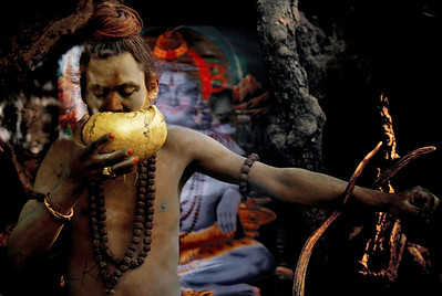 Shaivite sadhu drinks from his human skull bowl. A picture of Shiva can be seen behind him. Although the practice of taking all of one's food and drink from a human skull is rare nowadays, certain sadhus, particularly the Aghori sub-sect, still hold to it as a daily reminder of human mortality and as a challenge to transcend the duality of life and death. The Aghori subsect was founded by Brahma Giri, a disciple of Gorakhnath and are strict followers of Shiva. These ascetics remain naked and often wear a rosary made of bones around their neck and carry a human skull in the left hand and a bell in the right hand. Their sectarian tilaka, forehead mark denotes unity of the Hindu triad. Generally, they are recruited from the lower castes.  Pashupatinath, Kathmandu, Nepal.