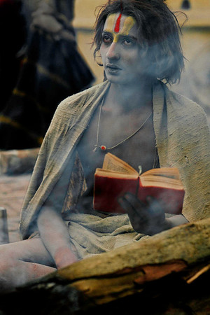 "A young sadhu reads holy scripture near the fire. Worship is part of daily life. Some sadhus chant powerful mantras. The Gayatri Mantra is one of several mantras which are sacred incantations or mystical forumlas of ancient literature. The Gayatri Mantra was given by Brahma and mentioned in the Rigveda and is named after the consort of Brahma:  ""O that glory- of Savitri most high. Oh Divine let us mediate upon you. May it inspire understanding.""  The goal of the recitation is to attain God realization. Practice can lead the mind into a transcedental union with the deity. Pashupatinath, Kathmandu, Nepal."