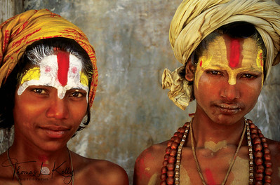 Two young Vaishnava sadhus with colorful tilakas, or forehead markings, inside the Pashupatinath Temple complex. The adornment of powdered paint is unique to each Sadhu and a sign of the Hindu Triads that he is a part of Renouncing his birth family for one of the Hindu Triads; he adopts Vishnu, Brahma or Shiva as his new family. Pashupatinath; Kathmandu; Nepal.