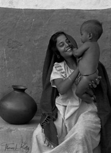 """MOTHERHOOD   Kailashi, a Badi mother, playing with her son. """"I was a beautiful child with curly hair. The high castes and """"big"""" people played with me and gave me rupees when I danced. My father made drums and my mother begged. And then we came here to this village and we did pessaa.  """"Later, my father died'.  Western Nepal."""