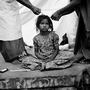 """RENUNCIATION  Former devadasis, now project workers for the Devadasi Rehabilitation center, untangle and cut the dreadlocks of a young devadasi, symbolizing her rejection of the practice.   Over 5,000 girls under twelve years of age are offered as grooms to ritually """"marry"""" the goddess in an ancient rite which some believe is more of a curse than a blessing. A daughter dedicated to the Goddess does not require an expensive dowry. A wealthy patron may pay impoverished parents to dedicate their daughter to Yellama so that the patron may receive a boon from the deity.   Saundatti, Karnataka, India."""