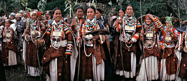 Nyinba women dressed with elaborated turquoise jewellery participate in the polyandry marriage ceremony by dancing and singing as they receive the Nyau, representatives of the groom. Many societies in the Himalaya practice polyandry, with women free to marry several husbands, generally set of brothers. it is a clever adaptation in lands of spare resources, as it secure the labor of several ,en to support a family, even as it limits family size, and thus, the human impact on the environment. But it is also a simple choice, for there are many harsh environments where polyandry is not the norm. Marriage rules are sensitive touchstones of culture.  1986.   Humla, Northwest Nepal.