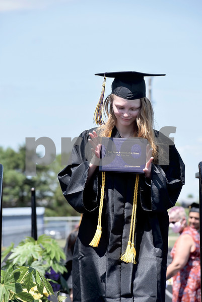 -Messenger photo by Chad Thompson<br /> <br /> Megan Gilbert looks over her diploma as she walks off the stage during the Eagle Grove High School class of 2020 commencement on Saturday.