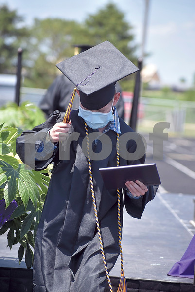 -Messenger photo by Chad Thompson<br /> <br /> Lance Hennigar hangs onto his tassel and diploma as he walks off the stage during the Eagle Grove High School class of 2020 graduation ceremony on Saturday.