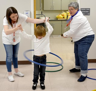 Paraprofessionals Jessica Mathis, left, and Judy Wall, right, spin a Hula Hoop around kindergartner Hunter Foss during the Early Learning Center's 1950s-themed Halloween celebration Thursday. Kaitlin Cordes photo