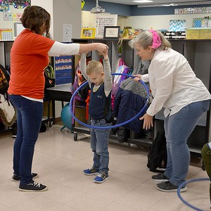 Parent volunteer Megan Farrar, left, and paraprofessional Julie Hodges, right, help kindergartner Pearce Beccue, center, Hula Hoop during the Early Learning Center's 1950s-themed Halloween celebration Thursday. Kaitlin Cordes photo