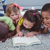 Happy kids reading a book together