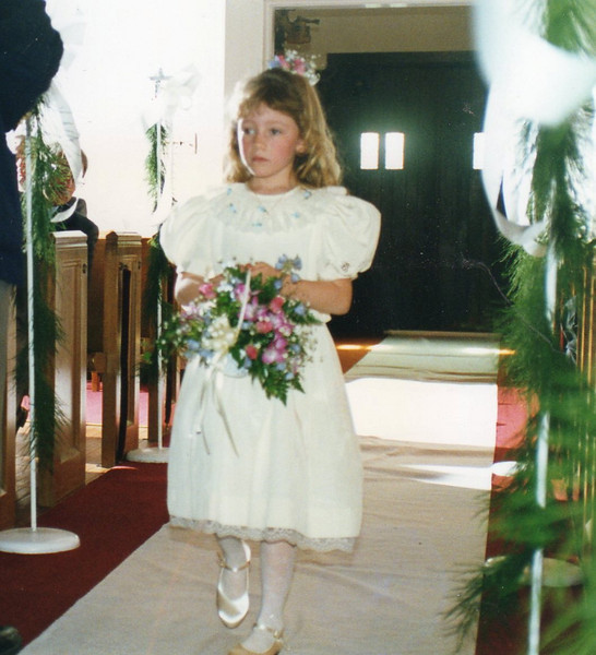 The flower girl comes down the aisle.