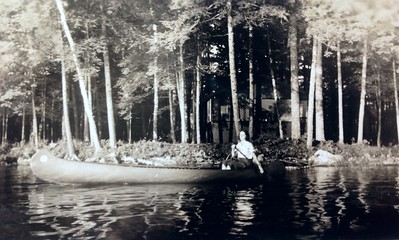 Joanna Stone canoeing in front of the cabins, early 1930's