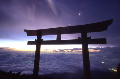 The moon and Venus hover above the welcoming  torii (gate) to the summit of Mt. Fuji before sunrise.