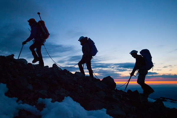 MT RAINIER, WA - Climbing the south rim of the crater just before sunrise to gain the 14,410' summit - Columbia Crest.