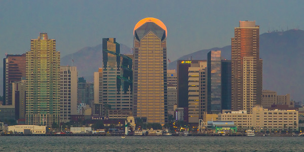 The full moon rises behind One America Plaza in downtown San Diego