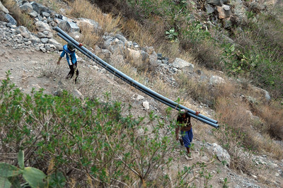 COLCA CANYON, PERU: Local labor carry pipe sections down into the canyon for continued development projects.