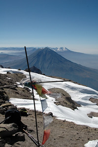 CHACHANI, PERU: The summit - 6,075m - marked with a cross and the now world wide symbol of mountaineering, prayer flags from Nepal. El Misty in the background.