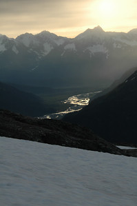 The braided river way down in the valley catches and reflects the golden glow of the sunrise.