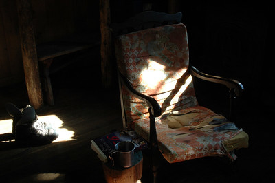 The rocking chair and book with boots drying in the morning sunbeams.