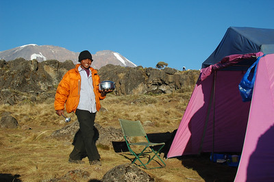 KILIMANJARO: Striker, our server brings our first course of dinner, cream of cucumber soup. Kibo summit behind him.