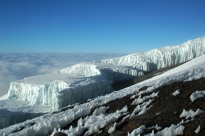 KILIMANJARO, TANZANIA, AFRICA: Fading glacial ice columns above a sea of clouds stretching out over Africa.