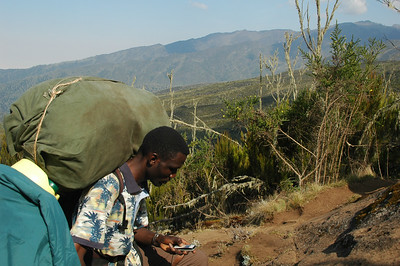 KILIMANJARO: Even on the slopes of Kilimanjaro, communications technology is present. These porters get a gig like this once a month or so which takes them away from what ever other work they have. They are all drawn from a porters association which works much like a union and helps protect them from abuse and mistreatment.