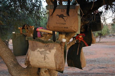 Our water bags are cooled by evaporation as the water slowly seeps out of the swollen canvas. The bags will often be hanging in trees like this because they leak and get dirty (not good for the evaporation process) when they get put on the ground.