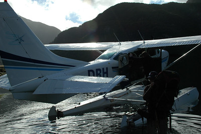 Derek retrieves his pack from the plane (baggage claim) while shin deep in the salt water of Dusky Sound.