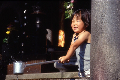 A young girl catches water at Kiyomizu Temple.