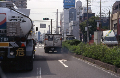 A Japanese fuel truck blasts out a plume of dark exhaust fumes as it accelerates to the green light.