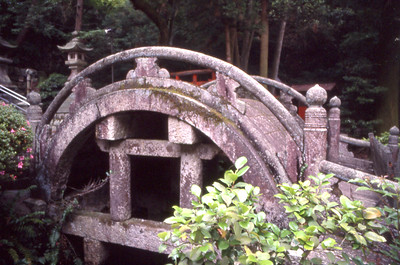 A decorative bridge in a garden leading to a shrine.