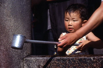 A youngster gets help to catch some water dripping from the fountain at Kiyomizu Temple.